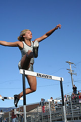 women jumping hurdle
